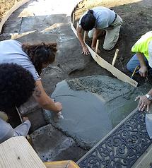spreading new concrete, filling in gaps.