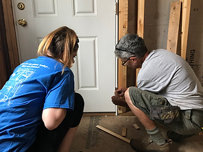 Construction team member Mary instructs volunteer on how to shim in a door.png