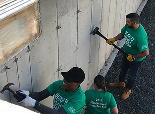 Citizens Bank volunteers hammer off the rebar pins used to secure the concrete forms-3.png