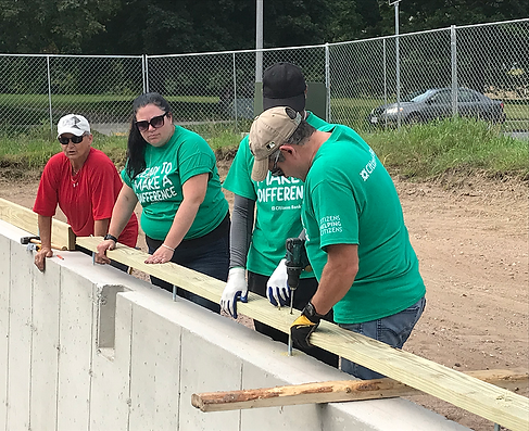 Citizens Bank volunteers work together to prep and install the sill seal and sill plate to