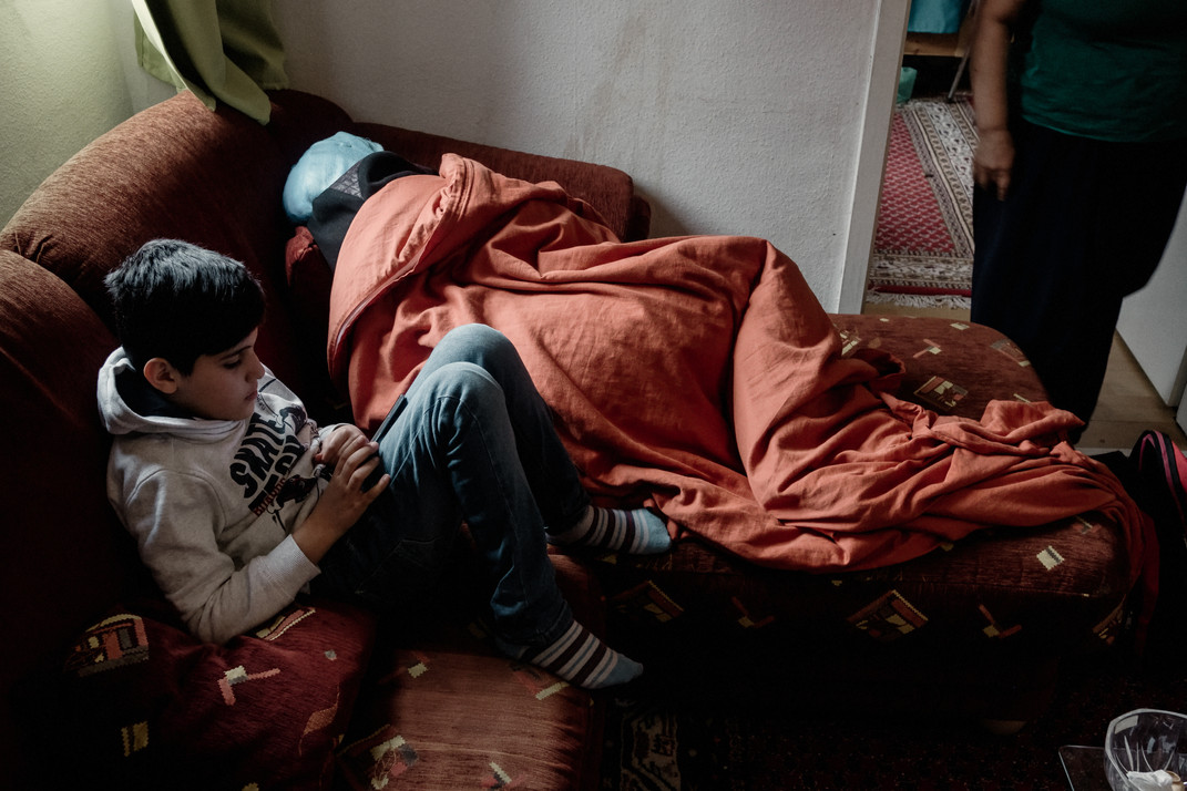 Baara joue avec le téléphone de sa mère, Amina est fatiguée et triste, elle attend le jour où sa famille sera réunie.  Baara plays with her mother's phone, Amina is tired and sad, she is waiting for the day when her family will be reunited.