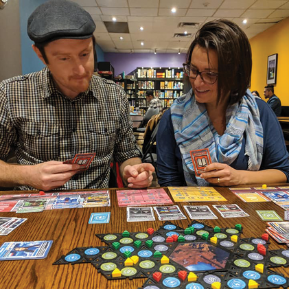 Two boad gamers playing Lander and contemplating their strategies
