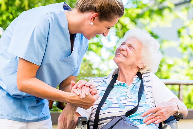 Nurse holding hand of senior woman in pe