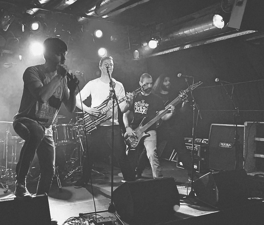 Quantum am SPH Music Masters im Werk 21. Bild von letztem Song Spartans. Mit den beiden Gitarristen an den Seiten und dem Bassisten in der Mitte stehend. Der Sänger setzte kurz danach zum brühmten Growl vor der Bridge an.