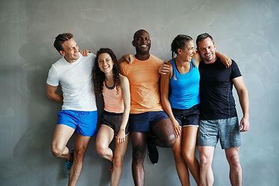 Smiling group of friends in sportswear laughing together while standing arm in arm in a gy