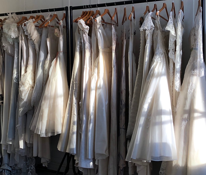 Couture wedding dresses on rail in studio