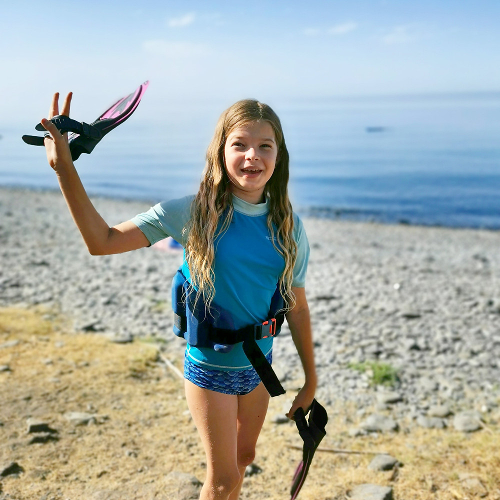 Rosie standing on a beach wearing a swim belt and holding flippers. She has a big smile on her face!