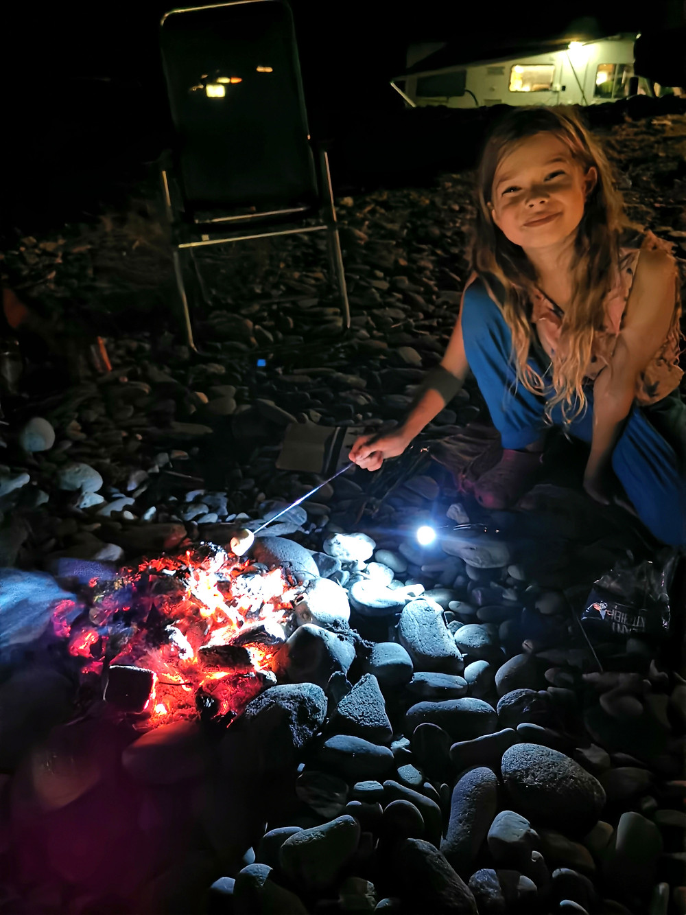 Rosie is sitting on a stone beach in the dark. There is a pile of glowing embers from a fire in front of her, and she is holding a marshmallow on a stick.