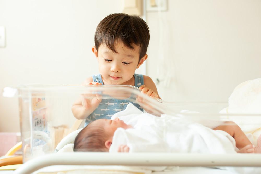 新生児を見る子供