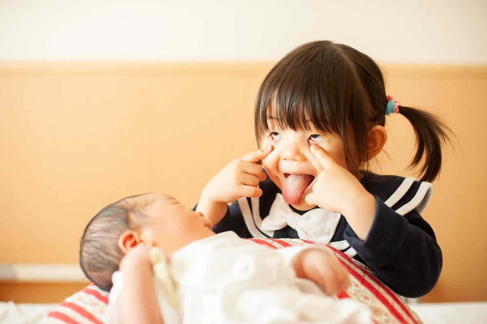 赤ちゃんに「あっかんべー」をするお姉ちゃん