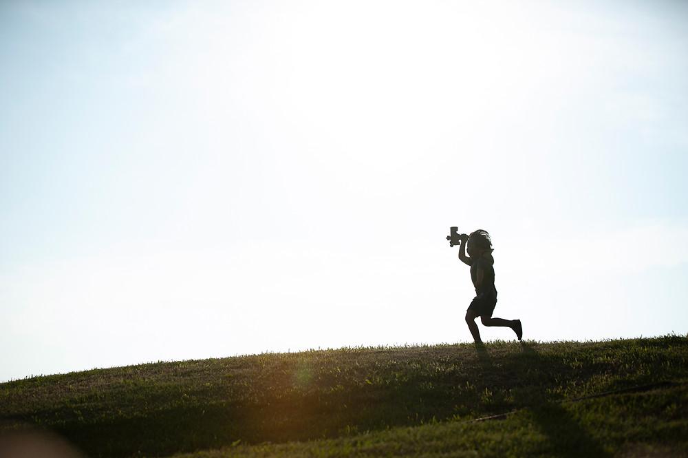 飛行機のおもちゃを持って丘をかけぬける男の子
