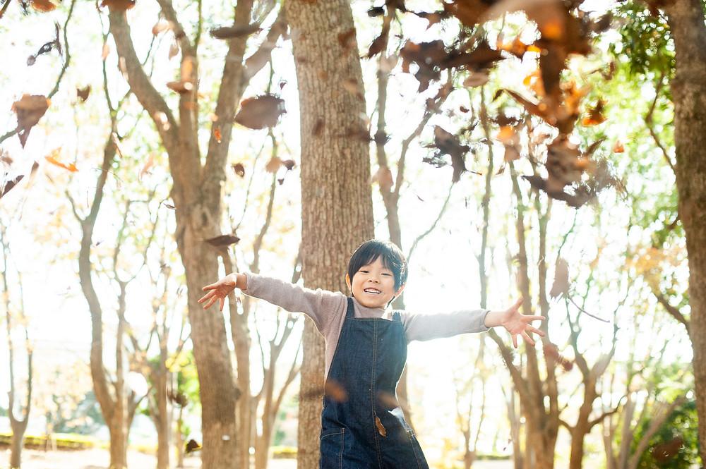 落ち葉を投げる少年
