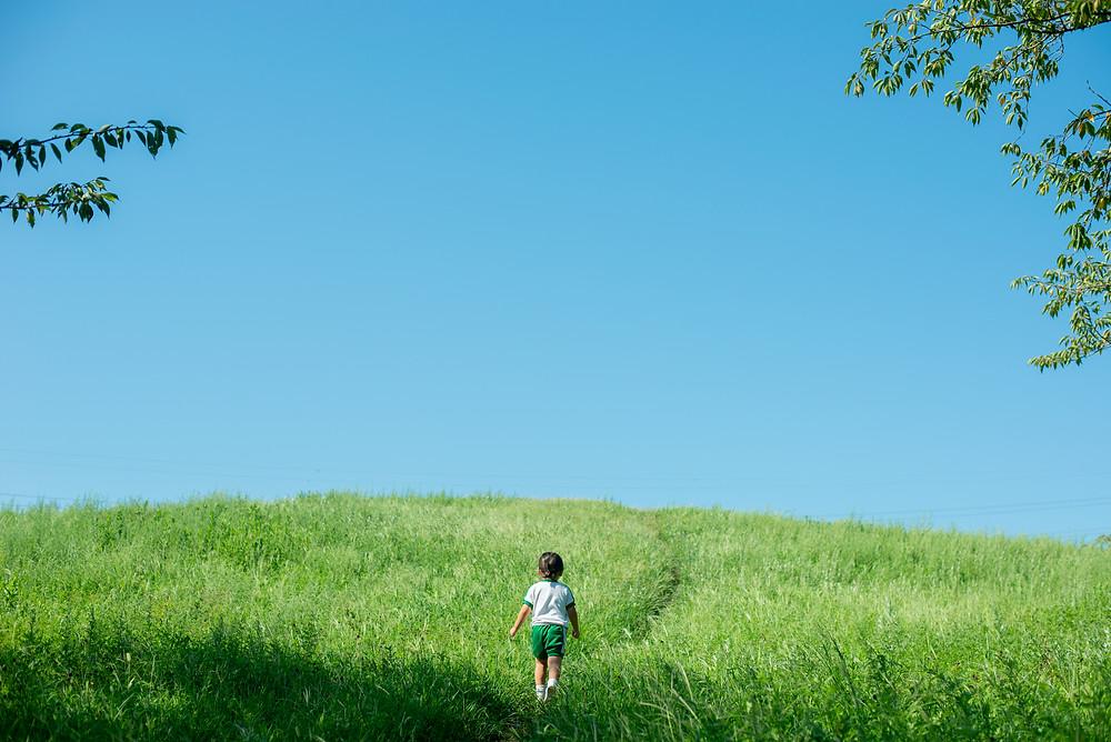 円服をきて丘を歩く幼児