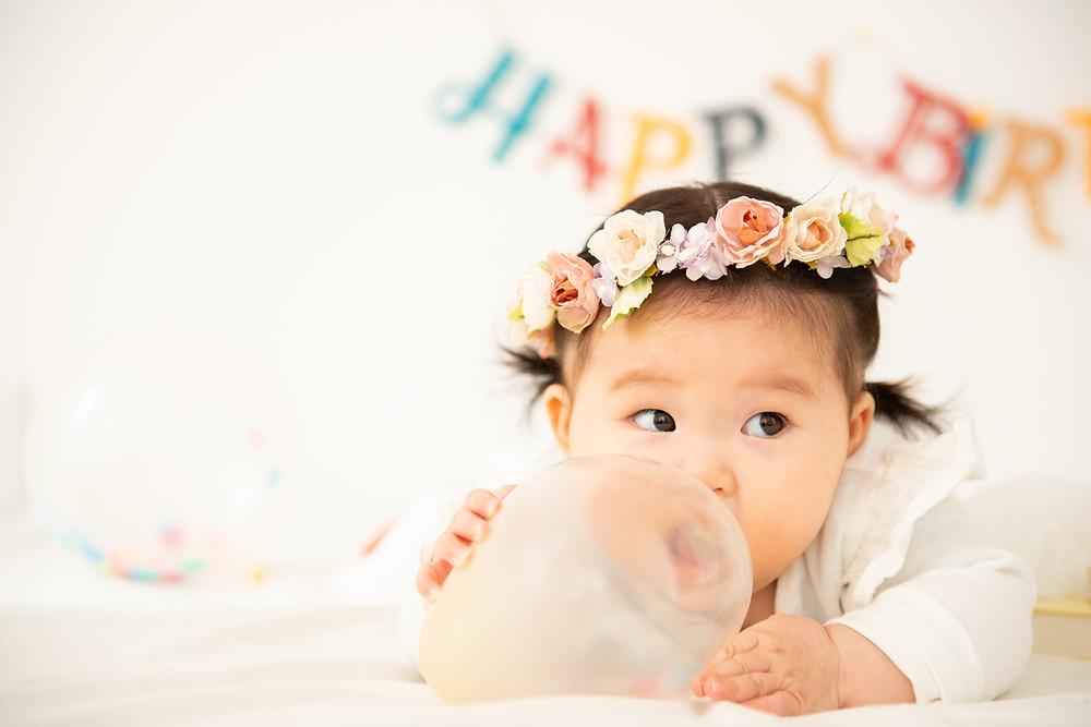 風船を咥える赤ちゃん