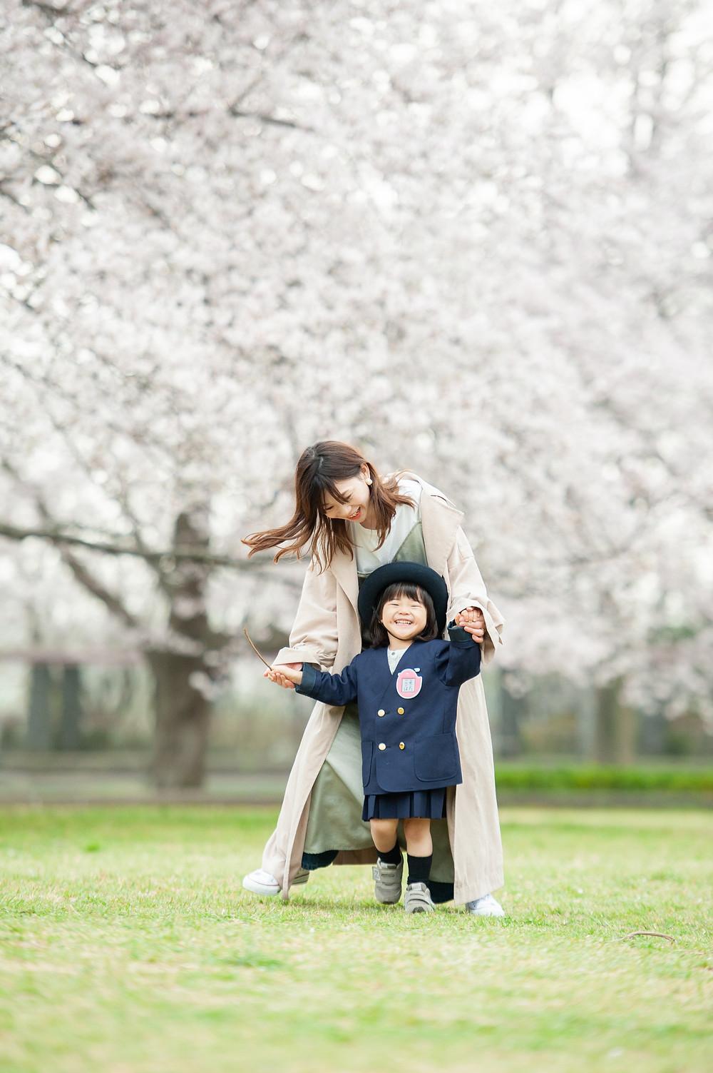 桜の咲く公園でママと一緒に歩く娘