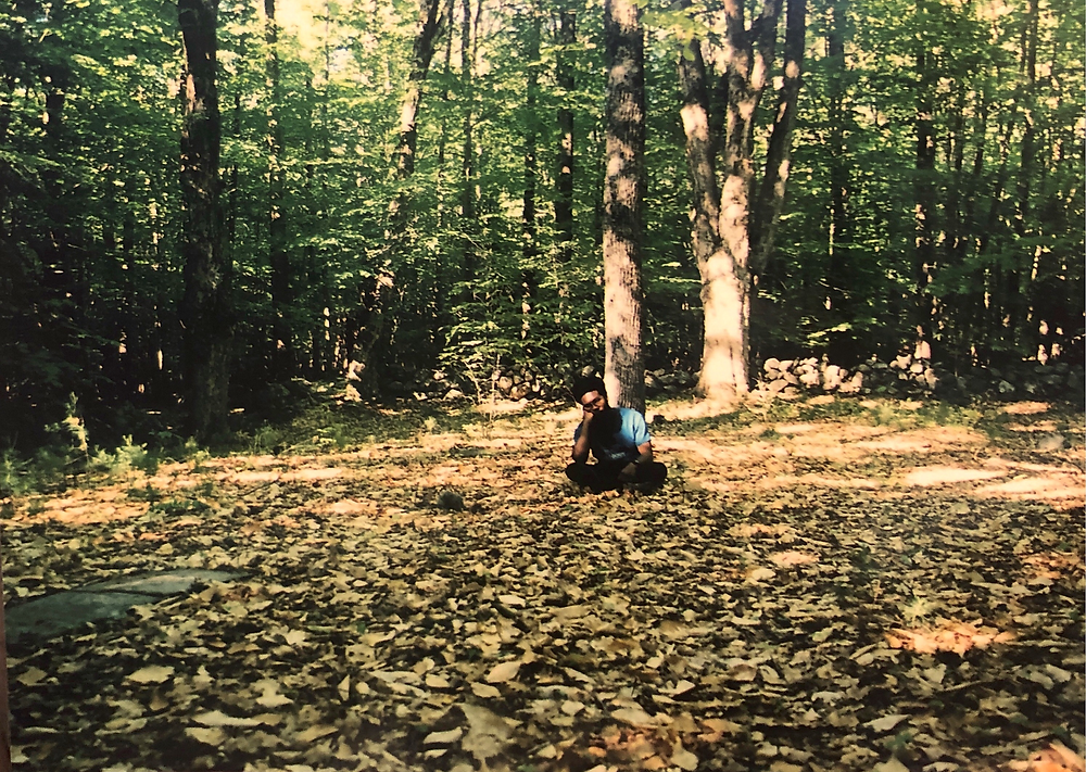A young man sitting down on a bed of grass in a New Hampshire forest