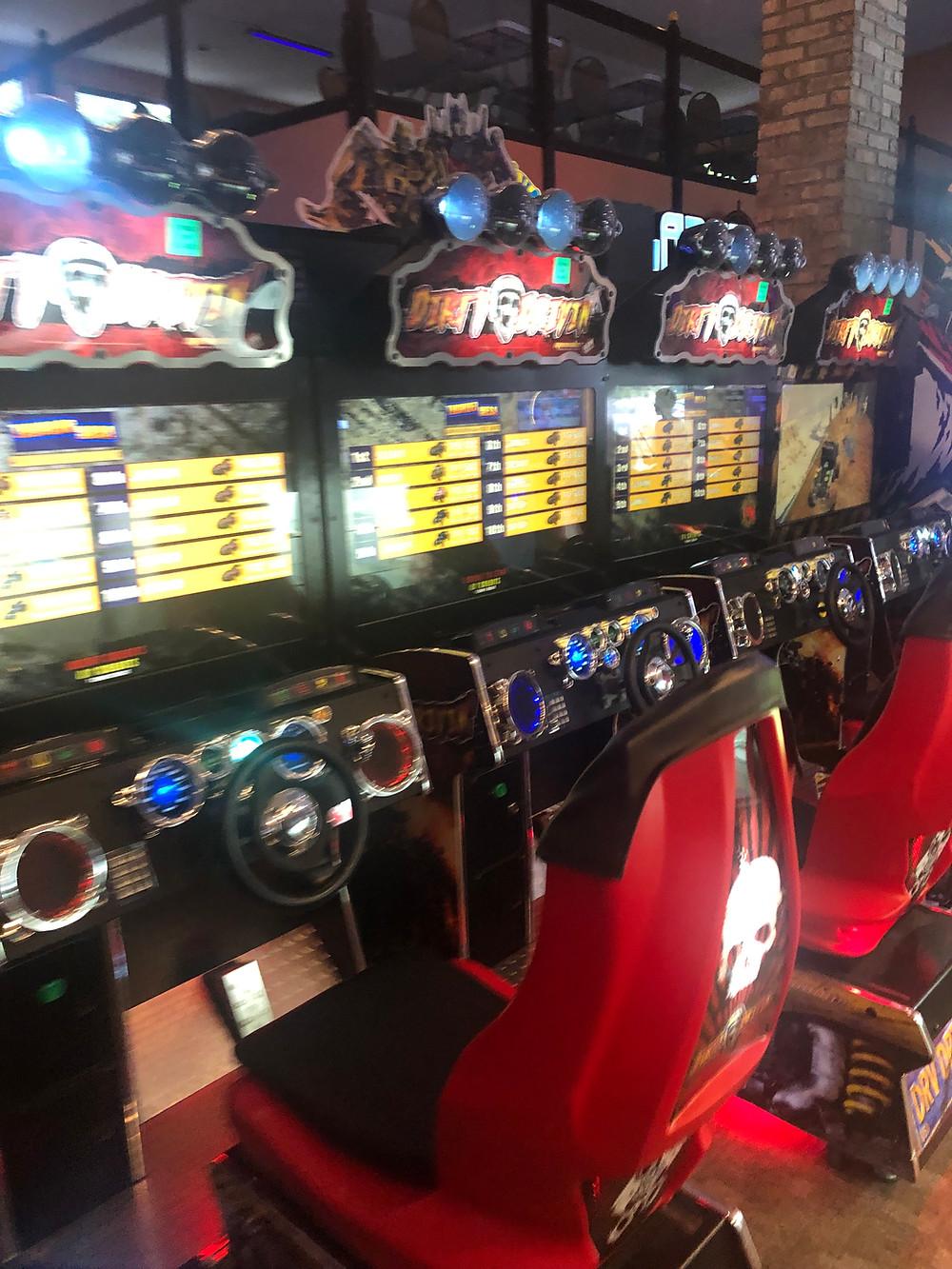A row of racing games at an arcade