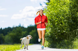 Young attractive sport girl running with dog in park.jpg