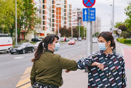 two-friends-walking-in-city-wearing-prot