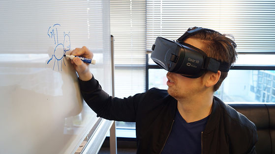 person-wearing-black-vr-box-writing-on-w
