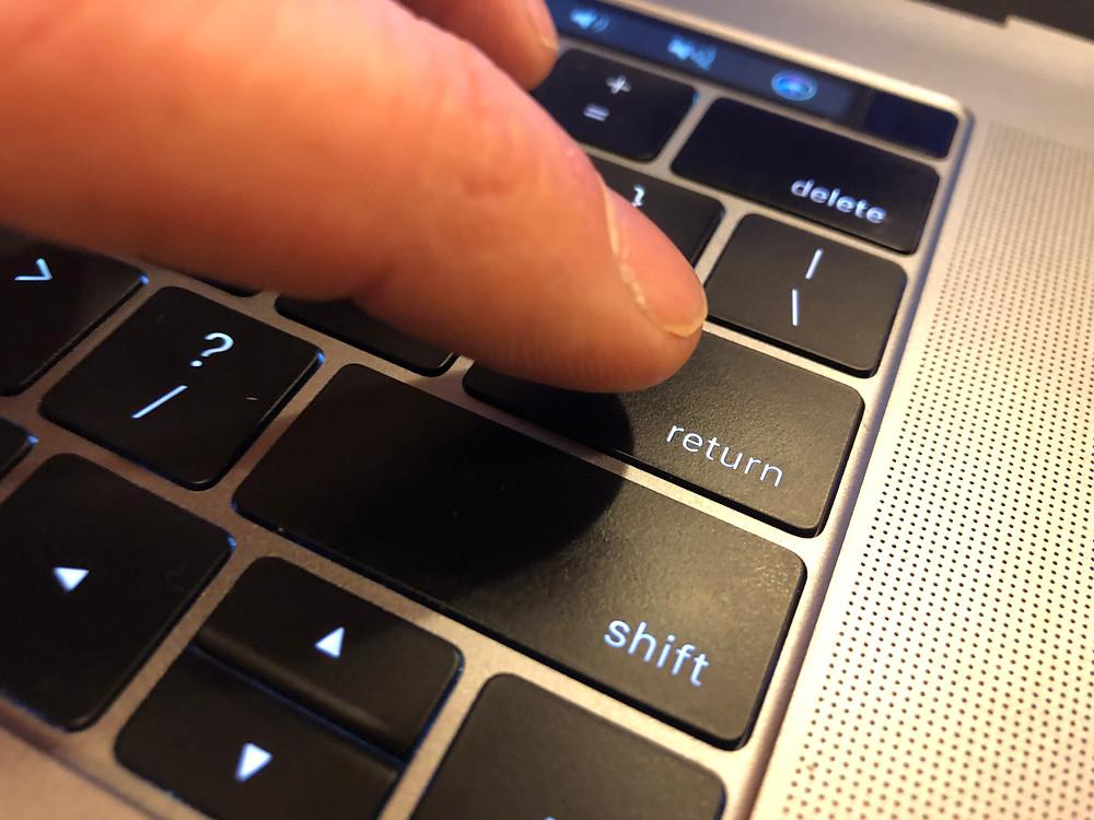 Finger pushing return button on keyboard