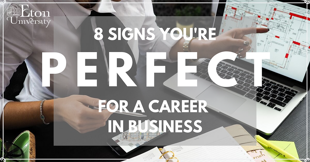 Text reads '8 signs you're perfect for a career in business' in front of a photo of a person writing notes and pointing to their laptop screen at a desk