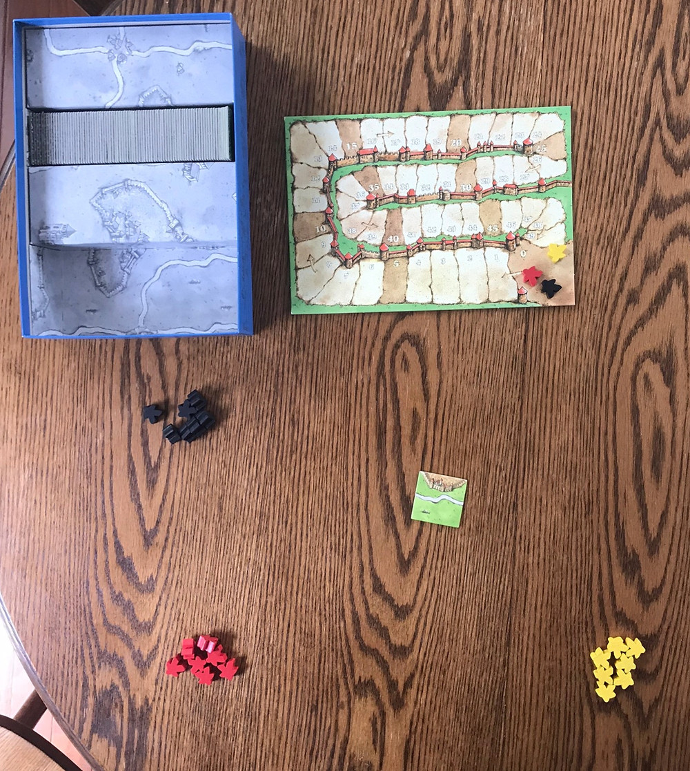 Here's a three-player game. The starting tile is in the center, the three players each have their meeple in a pile, the score board has everyone at 0, and the tile supply has been randomized and placed in the box. Some version of the game have a bag to draw tiles form, some people just leave them in a pile on the table, others arrange them into stacks . . . they're pieces of cardboard, you can do whatever you like.