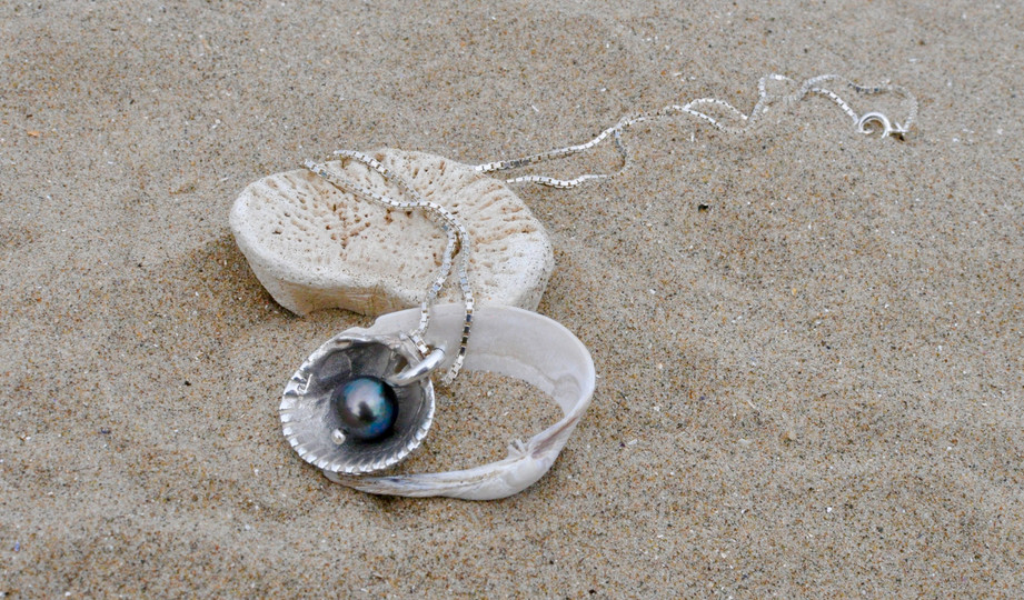 Precious Memories- A natural grey pearl dangles easily in this solid silver shell. Our mother's favourite piece and imbued with our precious memories of her.