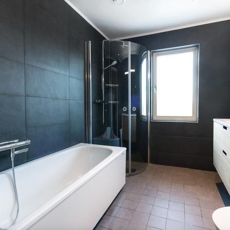 Badrumsrenovering med grått kakel och badkar