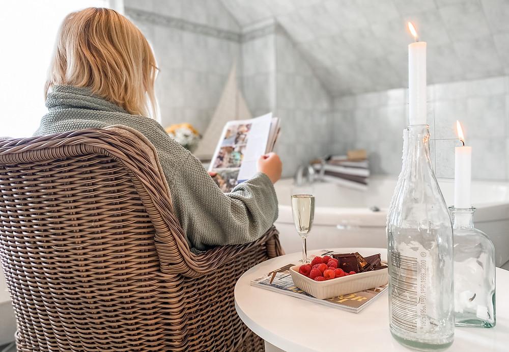 En kvinna sitter i en korgstol i ett badrum och läser en tidning. Bredvid henne står ett bord med levande ljus, ett champagneglas och en skål med hallon i.