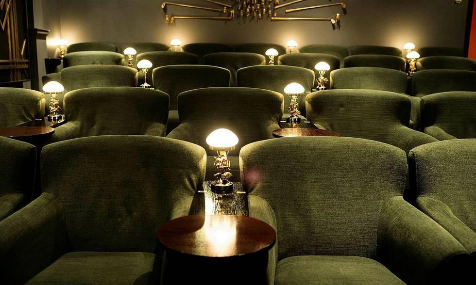 Gröna fåtöljer med små runda bord mellan och en liten lampa. Stilen är retro.