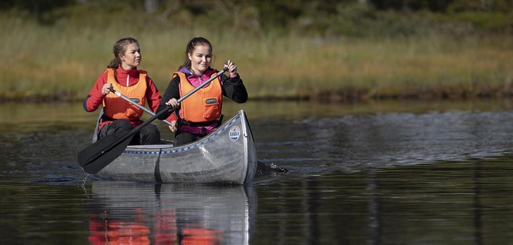 Två tjejer paddlar kajak men orange flytvästar.