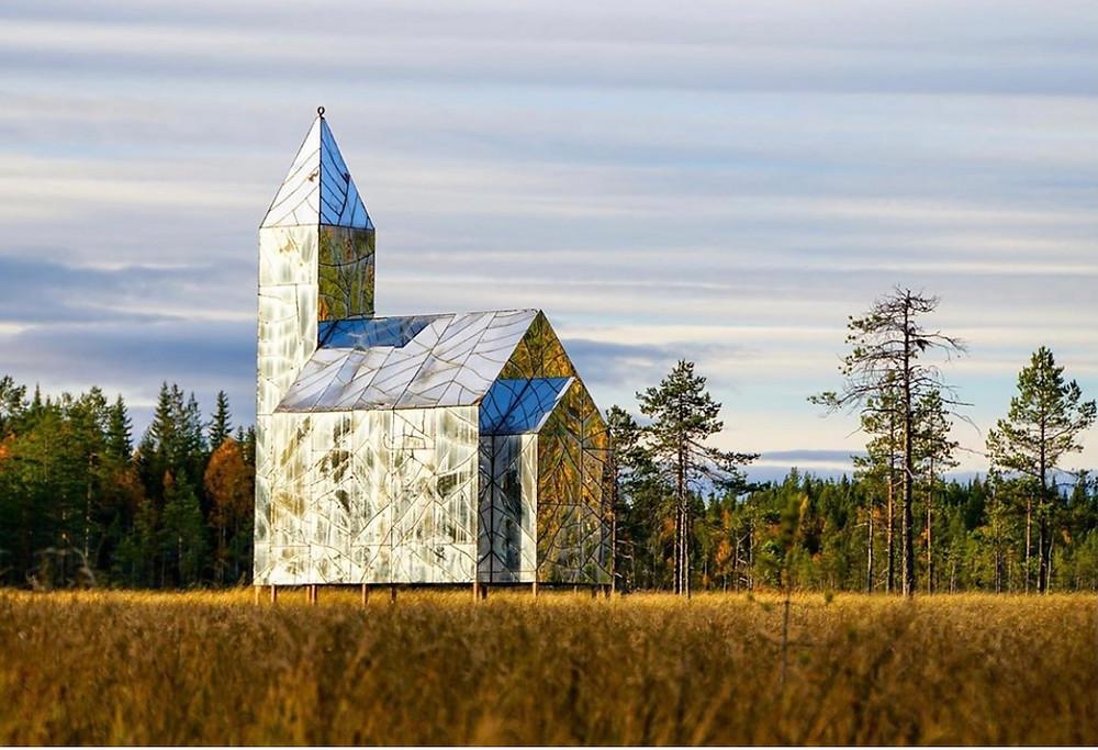 Konstverket Hägring, en kyrka byggd i sprucket glas som skiner i solen.