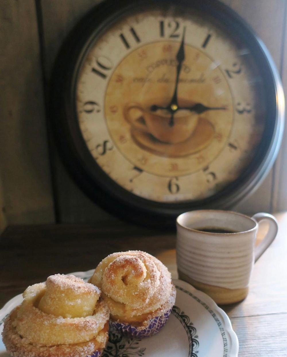 Två sockrade vetebullar med enrustik kaffekopp med en stor klocka i bakgrunden.