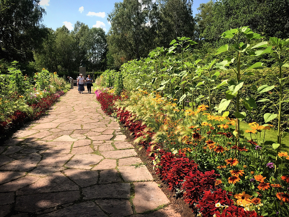 Stenlagd gång i Rottneros Park som ramas in med blommor i rött och orange.