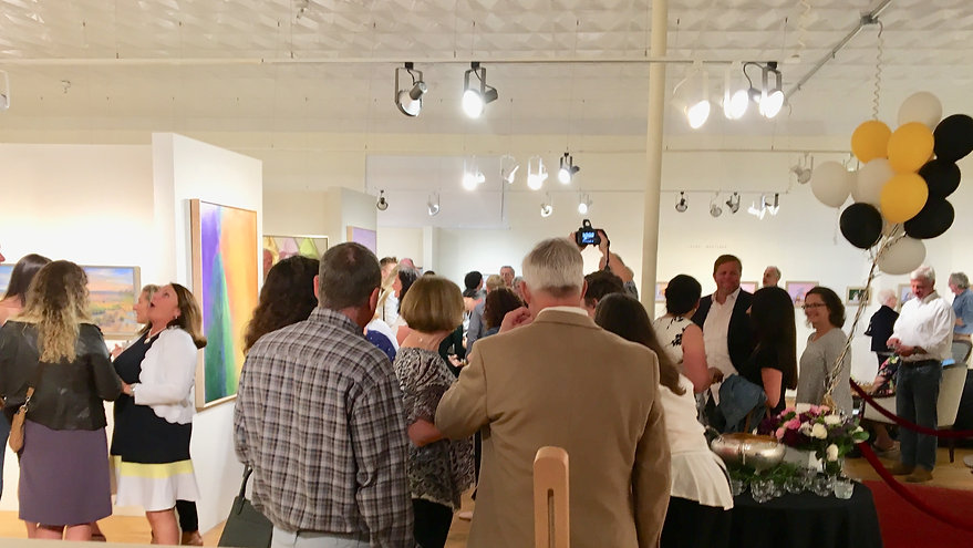 A crowd in the gallery celebrating a private event.