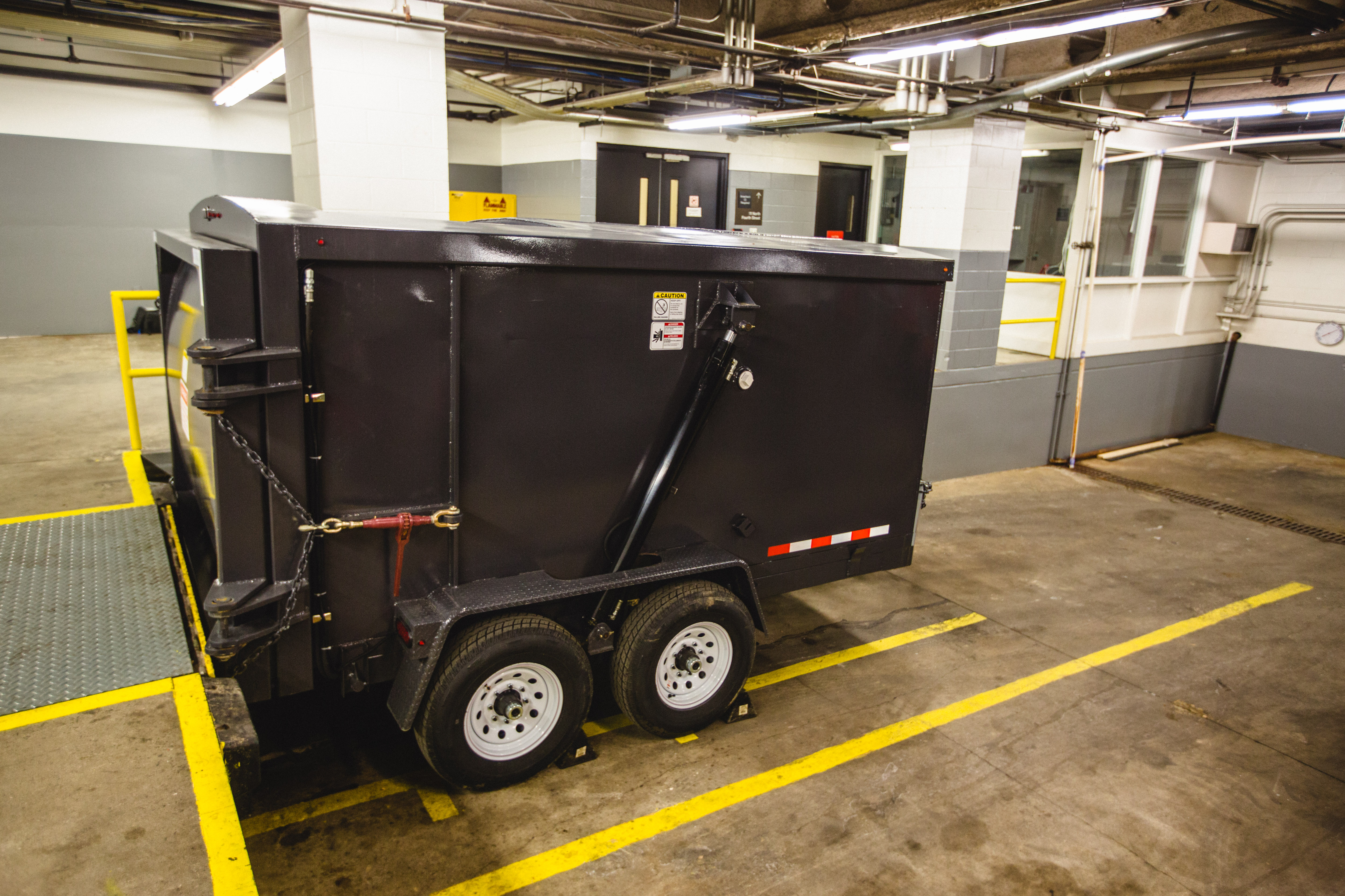 When the Qube Trailer is at a loading dock, waste materials can be manually loaded into the hopper on top of the Qube Trailer. This meets the minimum ISHA sill loading height requirements; simple and without any gates of electrical interlocks.