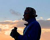 Marine biologist Tom Jefferson stands with binoculars and microphone, a sunset sky is in the background.