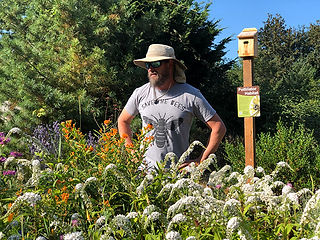 """Joe Dlugo standing behind a large clump of flowers of many colors. He is wearing a safari hat and a shirt that says """"save the bees.""""  Behind him is a birdhouse on a pole with a Xerces Society Pollinator Habitat sign."""