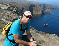 Marine biologist Tom Jefferson kneels atop a tall cliff overlooking the sea