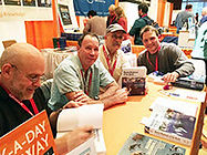 Marine biologist Tom Jefferson sits at a table with others, signing his book, Marine Mammals of the World