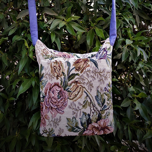 Bags made of tapestry with a long blue-gray handle and a zipper.