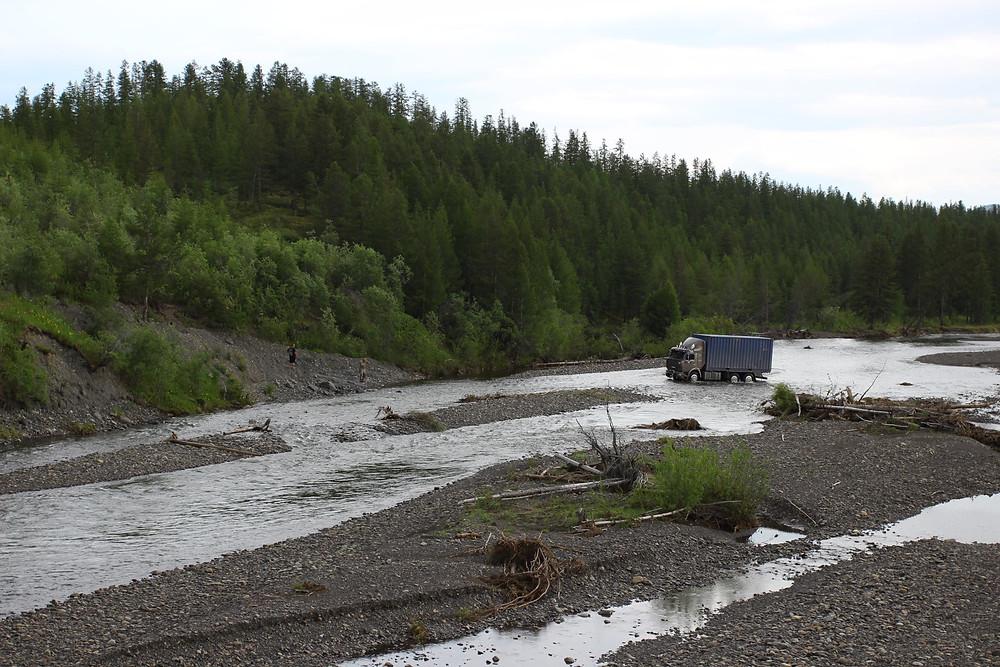Камаз тащит контейнер в обьезд смытого моста