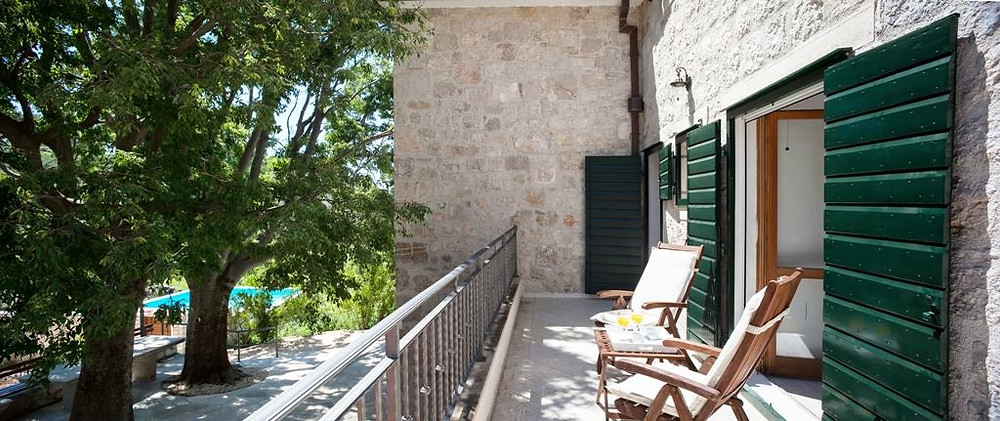 A stone house with green shutters is perfect to relax in after a day at the beach in Makarska Riviera