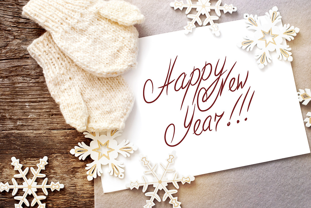 A wooden table with snowflake decorations, mittens and sign with the words Happy New Year!