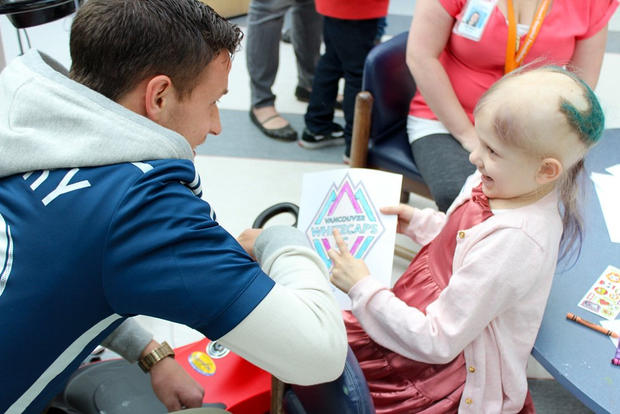 Ben McKendry enjoys a special moment with a patient at the BC Children's Hospital.