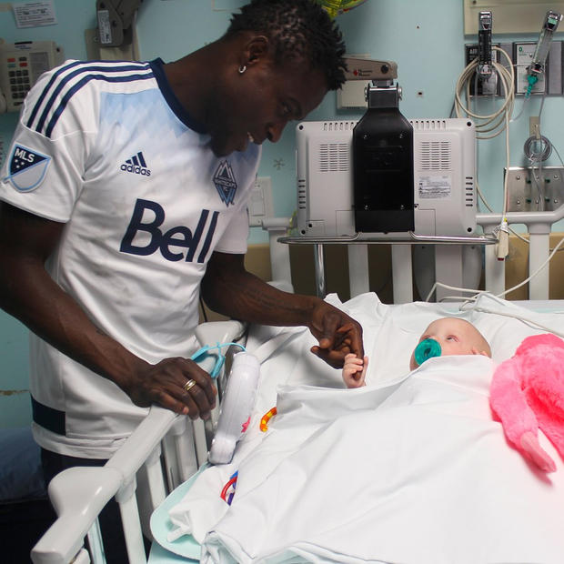 Gershon Koffie enjoys a special moment with a patient at the BC Children's Hospital.