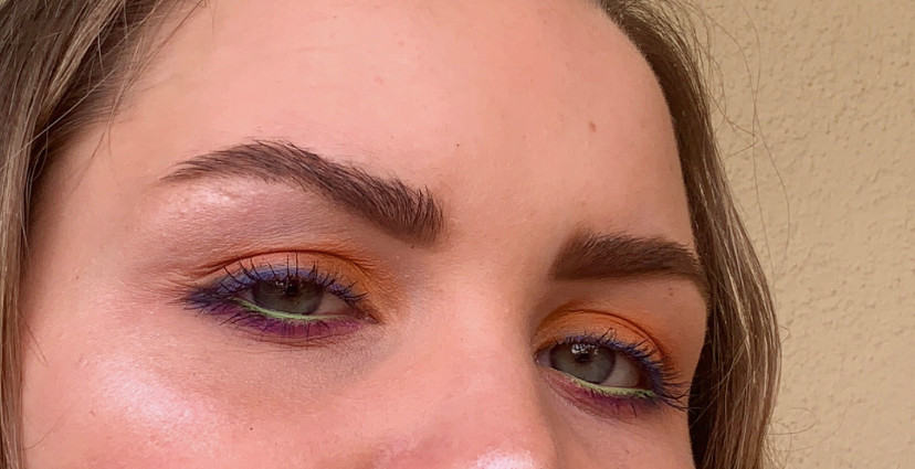 A closeup photo of an eye makeup look that uses rainbow colored eyeshadow