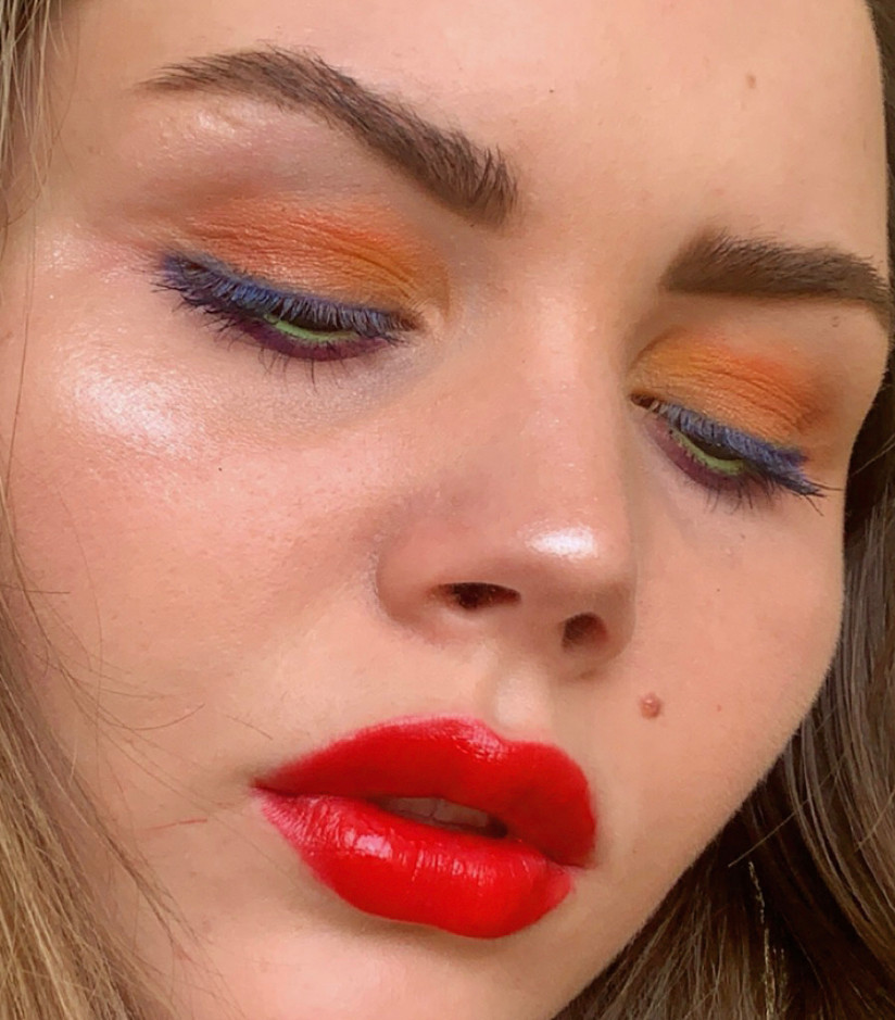 A photo of a makeup look that includes colorful, rainbow eyes and a red lip