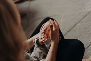 Newborn baby is asleep on their mother's lap with hands cradling their head showing the bond they share